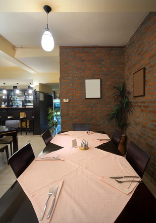 fine wood: Tables, chairs and brick wall, interior of a restaurant.  Stock Photo