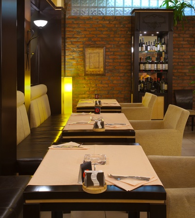 fine wood: Tables, chairs, brick wall and lighting equipment of a restaurant.