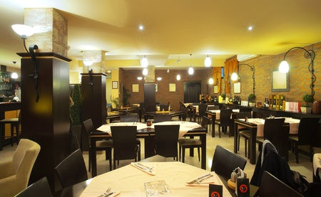 dining table and chairs: Tables, chairs, brick wall and lighting equipment of a restaurant.