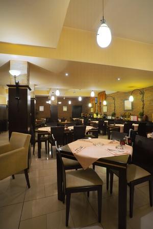 Mesas, sillas, pared de ladrillos y aparatos de iluminación de un restaurante.