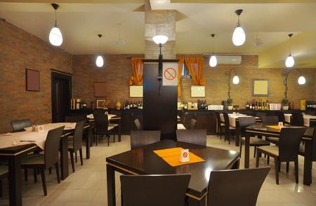 Mesas, sillas y muro de ladrillo, el interior de un restaurante.