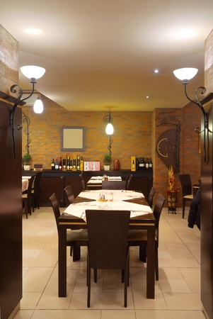 Tables, chairs, brick wall and lighting equipment of a restaurant. photo