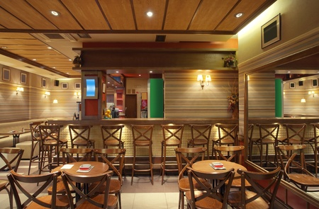 pub: Cafe interior with wooden furniture, lighting equipment and decoration.