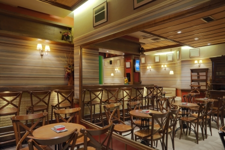 Cafe interior with wooden furniture, lighting equipment ,decoration and large mirror. photo