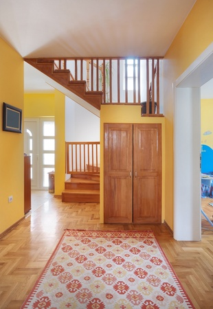 Entrance hall of a modern house, view on rooms and wooden stairs.  photo