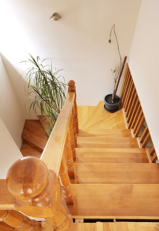 upstairs: Wooden stairs in house, interior decoration, wood and white walls. Stock Photo