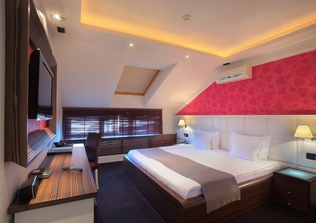 Interior of a hotel room for two, double bed and red wallpapers.