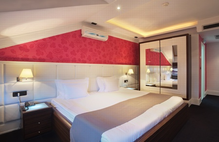 double bed: Interior of a hotel room for two, double bed and red wallpapers.