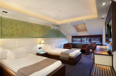 Interior of a hotel room for two, two beds and green wallpapers. Stock Photo - 10394779