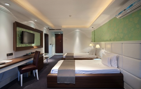 Interior of a hotel room for two, two beds and green wallpapers.