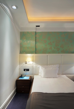 Inter of a hotel room for two, a bed and green wallpapers.  Stock Photo - 10394773