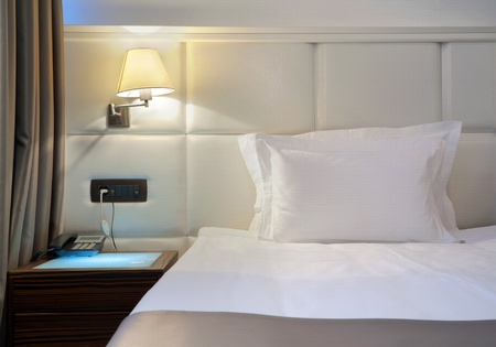 Hotel bed with white pillow and sheets, a lamp and a small table.  photo