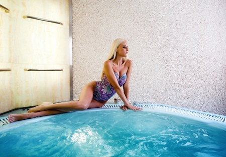 Pretty girl in a modern jacuzzi, seating and posing.  Stock Photo - 10962250