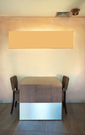 Table and chairs in a restaurant with empty frame on the wall.