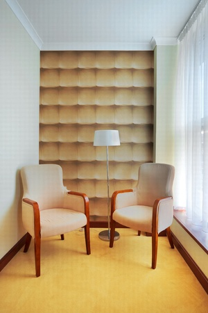 Interior of a hotel room, two armchairs and a lamp, beside the window.  photo