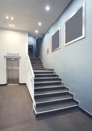 Interior of a building hall, hotel stairs, modern design in grey colors.  Stock Photo
