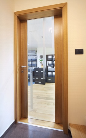 view through: Entrance of an office, view through wooden door on office interior.