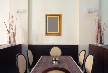 Just one corner of a restaurant, empty table and chairs with empty frame on the wall.  photo