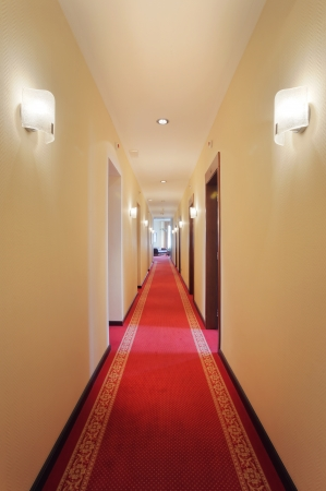 Interior of a hotel, view on a hall, classical look, doors and lamps.