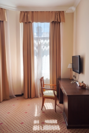 One part of a hotel apartment, vintage style, just a chair near the window.  Stock Photo - 14347269