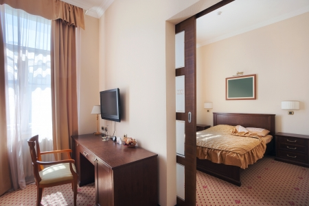 Interior of a hotel apartment, vintage style, view from living room to bedroom.