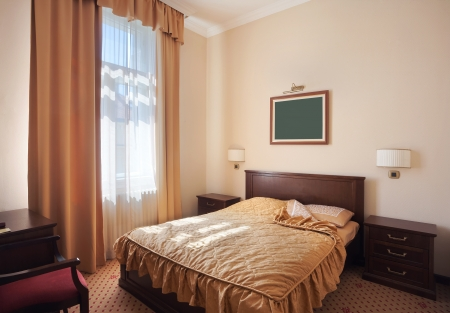 hotel door: Interior of a hotel room for two, just a bed near window.  Stock Photo