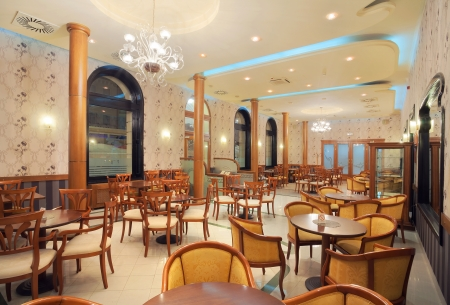Interior of a restaurant, vintage style, wooden classical furniture, retro wallpapers, during night.  photo