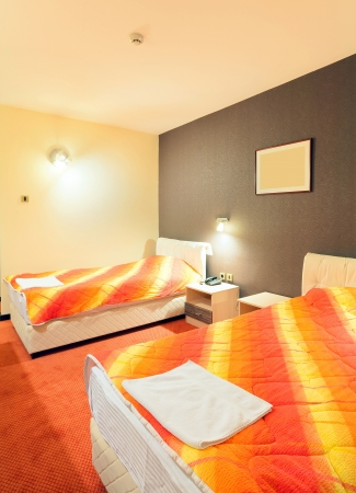 Interior of a hotel room for two, with furniture. Orange and brown colors as a main design details.  photo