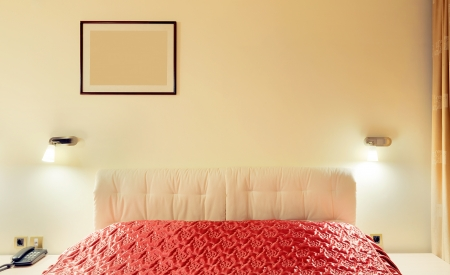 Details of a bedroom interior, night time, lights on, bed with red sheets.  photo
