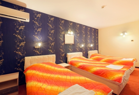 Interior of a hotel room for three persons, blue wallpapers and orange sheets on beds.  photo
