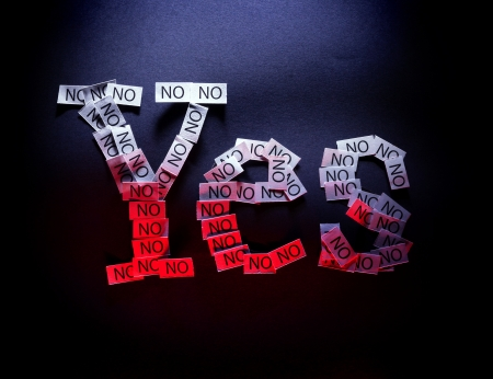 insincere: Word yes written of multiple noes on black background illuminated with white and red light