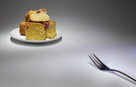 simple meal: Metal fork in one corner and some cakes on white plate in other corner