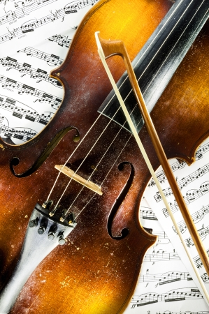 Details of a wooden old dusty violin and scores in background   Stock Photo - 17810443