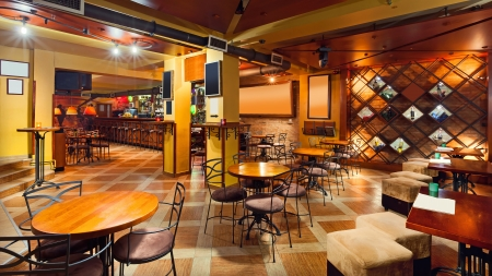 Interior of a modern pub in orange and wooden colors.  photo