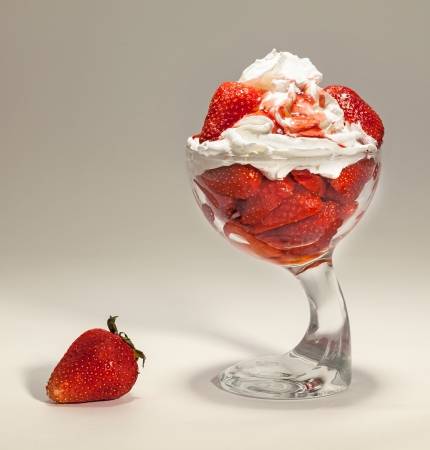 simple meal: Dessert of strawberries and cream in glass dish  Studio isolated