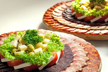Salad and pieces of various meat decorated and set on large wooden plate   photo