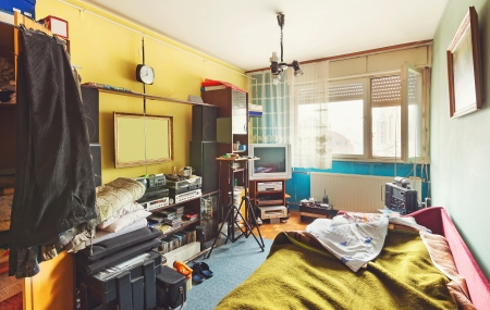Messy room interior, a lot of different stuff, from electronic appliances and furniture to clothes