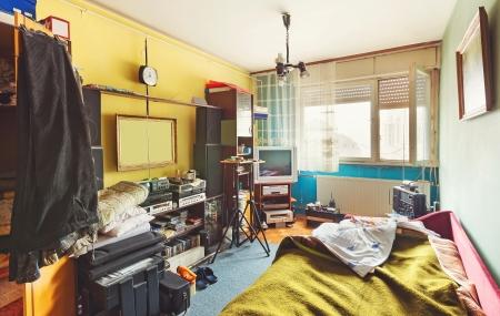 Messy pokoj interiér, spousta různých věcí, z elektronických přístrojů a nábytku oblečení