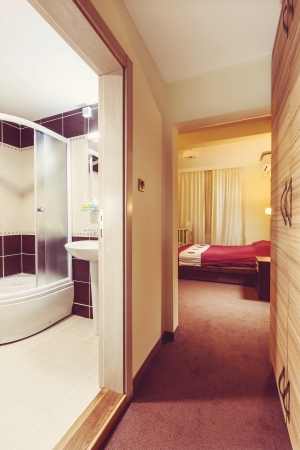 Interior of a hotel room, entrance with view on room and bathroom.  photo
