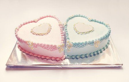 pink cake: Birthday cakes for twins, for a boy and a girl, shape of hearts   Stock Photo