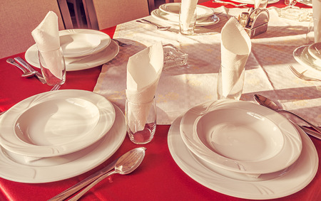 White empty plates and accessories on table with red sheets   photo