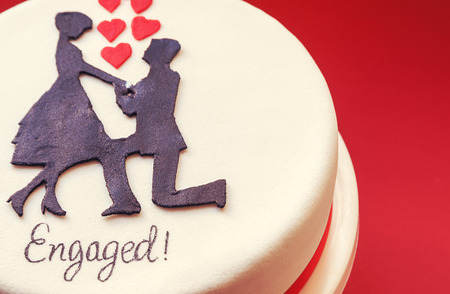 happening: White round cake on red background, decorated with male and female silhouette of sugar on top