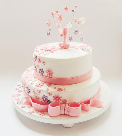 Torta per il primo compleanno decorata, con il numero uno in alto e le stelle intorno ad esso fatte di zucchero Archivio Fotografico - 28450243