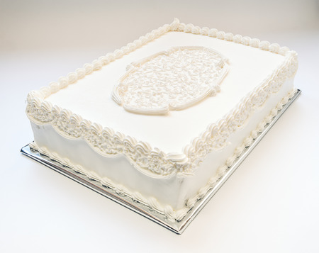ornamented: Simple wedding cake, all in white on gray background  Ornamented on top   Stock Photo