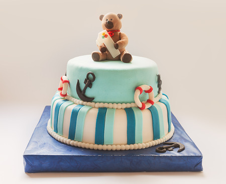 bear doll: Details of a first year birthday cake in blue, for boy.