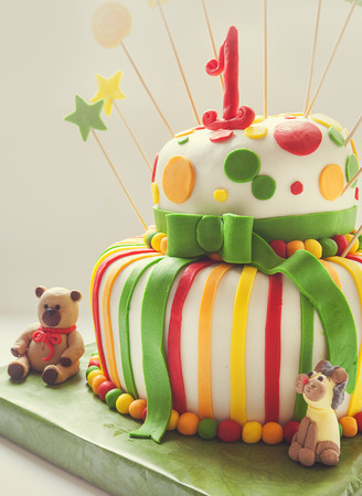 first birthday: Details of birthday cake, colorful decoration and number one on top.