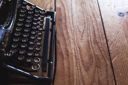 the typewriter: M�quina de escribir vieja de la vendimia en la mesa de madera, junto a la ventana. Foto de archivo