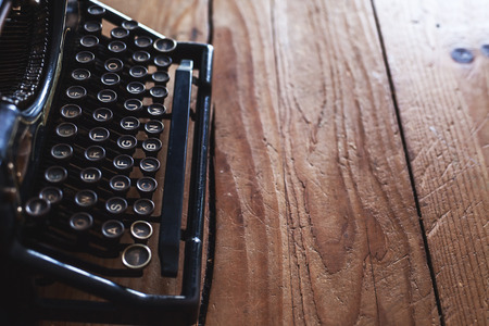 Old vintage typewriter on wooden table, beside window. Stock Photo