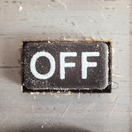 on off button: Old dirty and dusty rubberized button with written Off symbol on it, part of an old calculator. Stock Photo