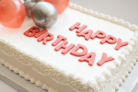 Details of a happy birthday cake, on white background.